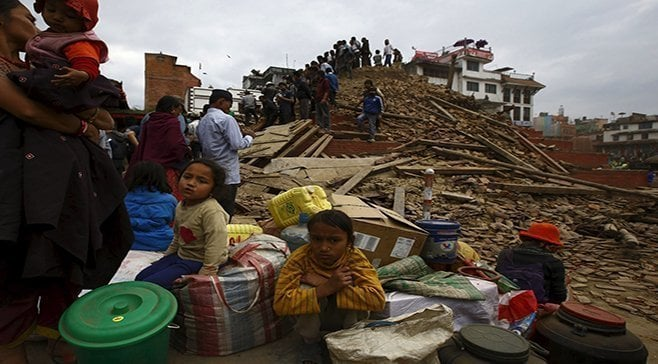 People sit with their belongings outside a damaged temple in Bashantapur Durbar Square after a major earthquake hit Kathmandu